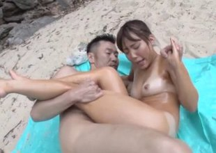 Curvaceous Japanese cutie gets surrounded with cocks on the beach