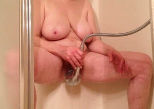 Breasty mature white lady in the shower room spraying her pussy